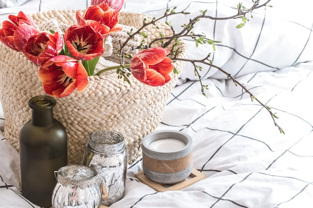 Przedmioty o przytulnym wystroju domu we wnętrzu pokoju. z pięknymi czerwonymi tulipanami. koncepcja wystroju i domowej atmosfery