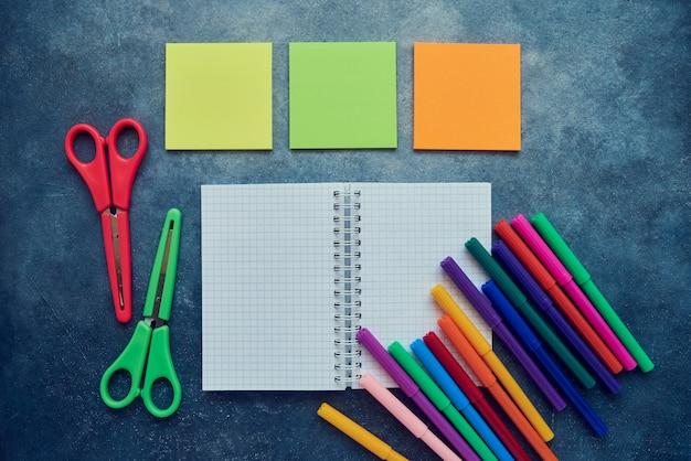 Przedmioty szkolne na ciemnym niebieskim tle. powrót do koncepcji szkoły. leżał płasko, kopia przestrzeń