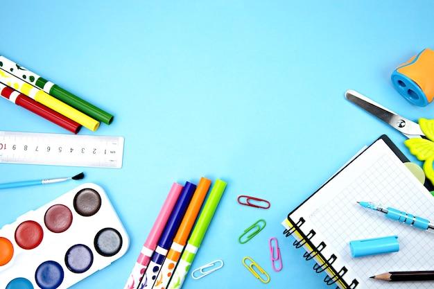Przedmioty szkolne na niebieskim tle. materiały biurowe