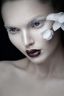 Przedni portret dziewczyny w modnym makijażu obok białego kwiatu