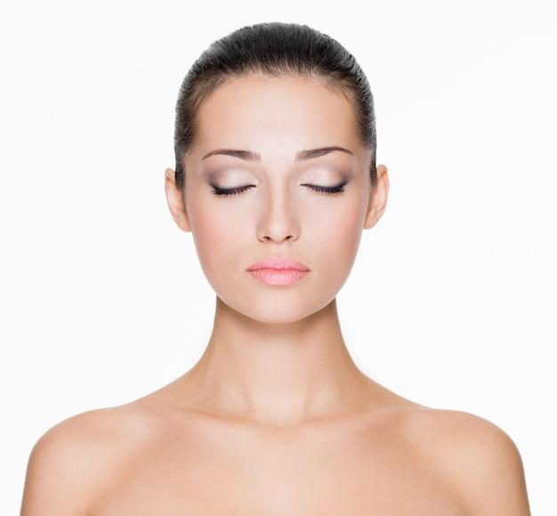 Przedni portret pięknej twarzy z pięknymi zamkniętymi oczami - na białym tle