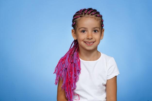 Przedni portret uśmiechniętej dziewczynki z różową fryzurą rudowłosą, ubrana w białą koszulkę, stoi na niebieskim tle. skopiuj miejsce. widok poziomy.