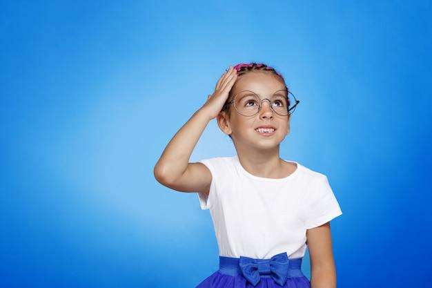 Przedni portret zdezorientowanej dziewczynki w wieku przedszkolnym w okularach na białym tle niebieska ściana.