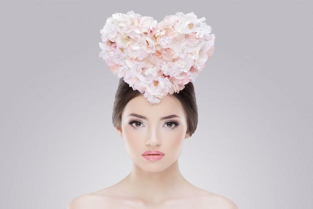 Przedni portret zmysłowej młodej kobiety niosącej kwiatowe serce