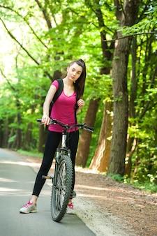 Przedni widok. żeński cyklista na rowerze na asfaltowej drodze w lesie przy dniem