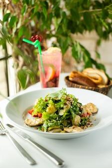 Przednia bliska widok świeżej sałatki z pokrojonymi warzywami i zielenią wewnątrz białej tablicy na białej podłodze