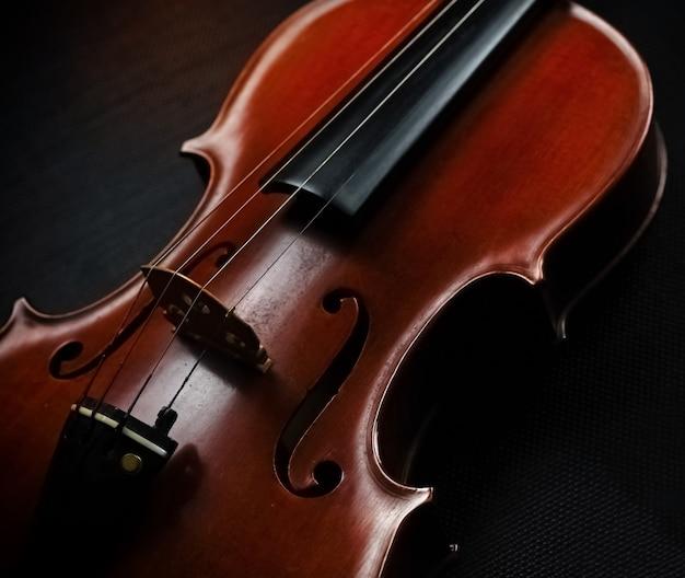 Przednia strona skrzypiec nałożona na czarne płótno, wokół rozmazane światło