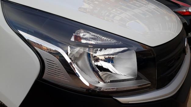 Przednie i przerywane reflektory nowej białej furgonetki.