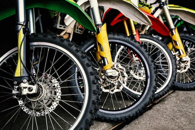 Przednie koła motocykli stoją w rzędzie.