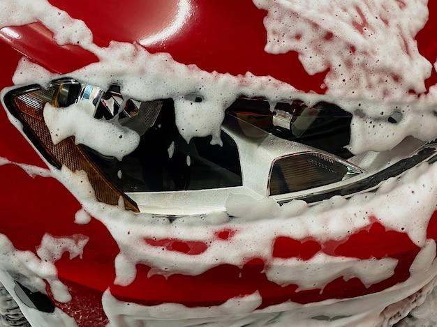 Przednie prawe koło czerwonego samochodu, na które nakładana jest pianka do mycia samochodu na myjni samoobsługowej.