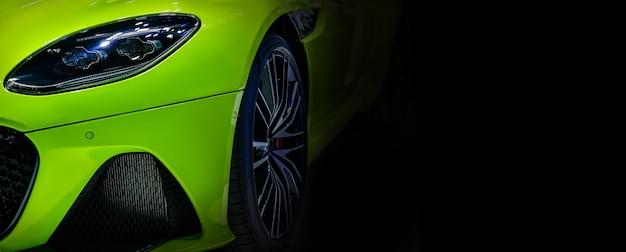 Przednie reflektory zielonego nowoczesnego samochodu sportowego na czarnej ścianie. wolna przestrzeń po prawej stronie