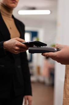 Przedsiębiorca dokonujący płatności zbliżeniowych za pomocą smartfona
