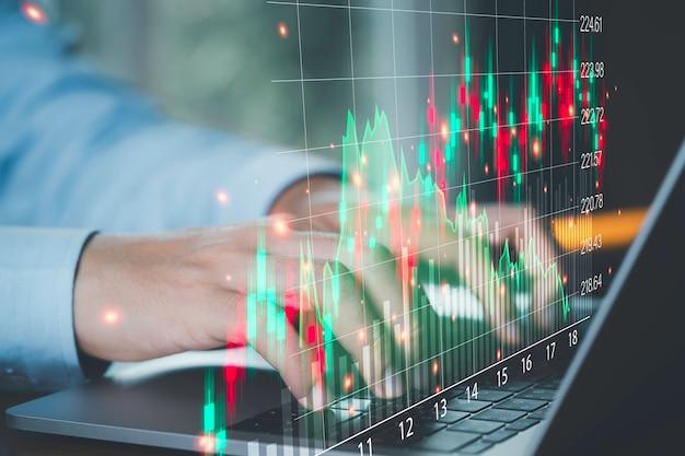 Przedsiębiorca handlowiec przy użyciu komputera przenośnego do analizy wirtualnego wykresu technicznego giełdy