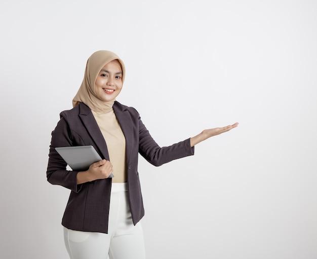 Przedsiębiorca kobieta ubrana w hidżab uśmiechnięta z trzymaniem tabletu pokazująca przestrzeń kopii, formalna koncepcja pracy