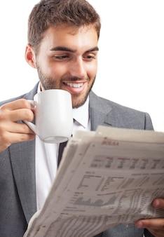 Przedsiębiorca korzystający gorący napój podczas czytania wiadomości