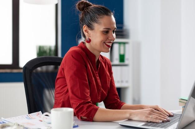 Przedsiębiorca korzystający z laptopa w miejscu pracy w biurze firmy, wpisując informacje o projekcie ...