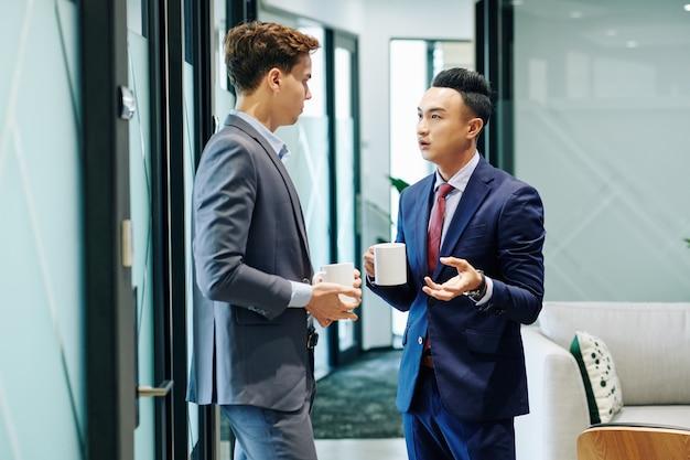 Przedsiębiorca omawiający plotki z kolegą