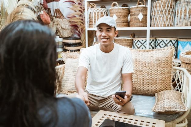Przedsiębiorca rzemieślniczy i klient uzgadniają, ściskając ręce podczas trzymania smartfona w galerii rękodzieła