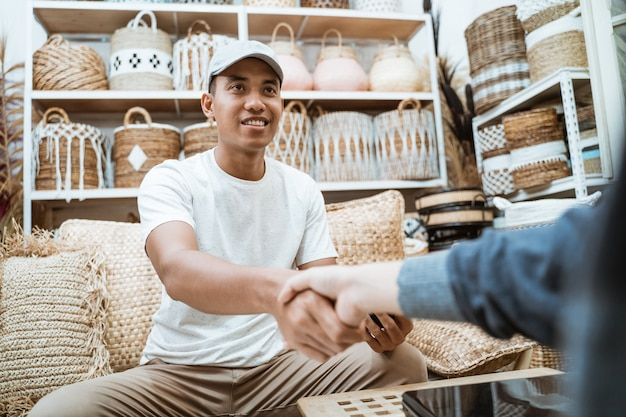 Przedsiębiorca rzemieślniczy zawiera porozumienie, ściskając dłoń, trzymając smartfon w sklepie rzemieślniczym