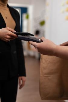 Przedsiębiorca używający smartfona do transakcji pieniężnych bez karty, do zabawy w dostawcę przynoszącego w papierowej torbie świeży, pyszny posiłek. klient odbierający jedzenie na wynos w miejscu pracy.