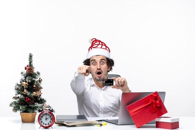 Przedsiębiorca w kapeluszu świętego mikołaja i trzymając swoją kartę bankową, patrząc i wskazując coś z zaskoczenia w biurze