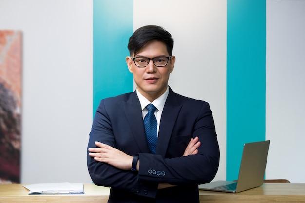 Przedsiębiorca wynajmujący samochód lub mieszkanie w niebieskim garniturze i okularach stoi ze skrzyżowanymi rękami