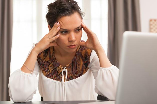 Przedsiębiorca z bólem głowy podczas pracy na laptopie z domowego biura.