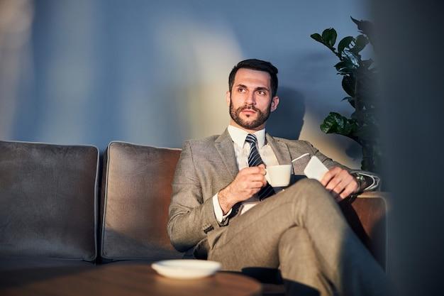 Przedsiębiorca z brodą delektujący się kawą
