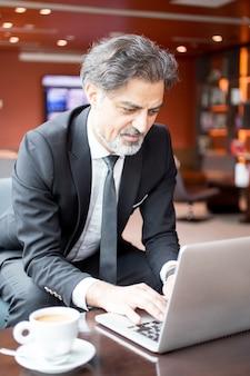 Przedsiębiorca zajmujący się treścią pracujący na laptopie w holu