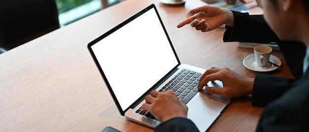 Przedsiębiorców przy użyciu komputera przenośnego z białym pustym ekranem przy stole spotkania