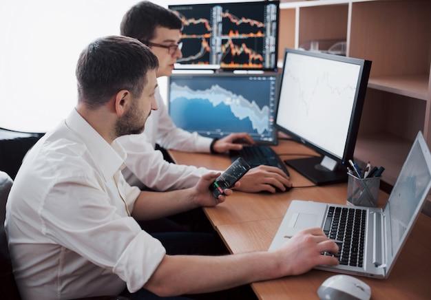 Przedsiębiorcy handlujący akcjami online. maklerzy giełdowi patrząc na wykresy, indeksy i liczby na wielu ekranach komputerowych. koledzy w dyskusji w biurze handlowców. sukces w interesach