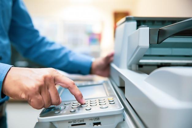 Przedsiębiorcy naciskają przycisk na panelu, aby użyć kserokopiarki.