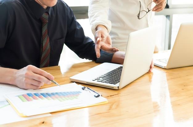 Przedsiębiorcy omawiają i analizują wykresy danych. praca w zespole mózgiem o udanym biznesie