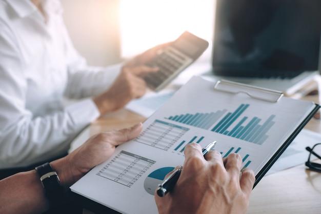 Przedsiębiorcy omawiają wyniki udanej pracy zespołowej.