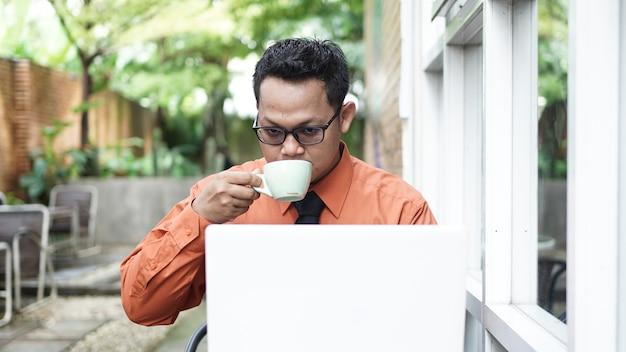Przedsiębiorcy pracujący przy komputerach, piją kawę i uśmiechają się