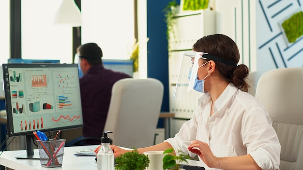 Przedsiębiorcy pracujący w maskach ochronnych w pokoju biurowym podczas koronawirusa. zespół w nowej, normalnej firmie finansowej, piszący na komputerze, sprawdzający raporty, analizujący dane patrząc na pulpit