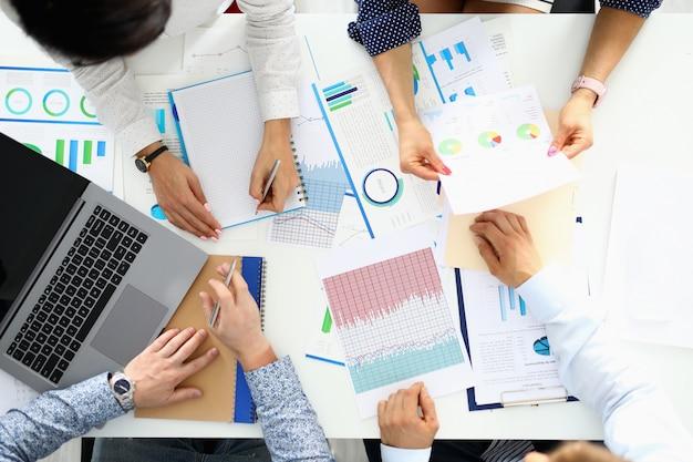 Przedsiębiorcy siedzą przy stole i omawiają wyniki biznesowe