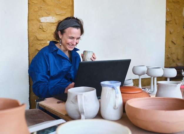 Przedsiębiorcza artystka uśmiechnięta przed laptopem w warsztacie