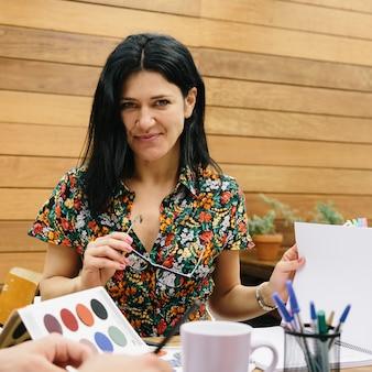 Przedsiębiorcza młoda kobieta przygotowująca projekt biznesowy w nowoczesnej przestrzeni coworkingowej