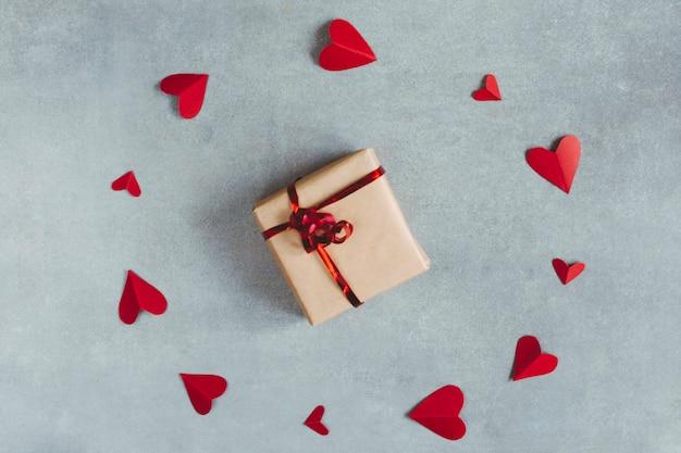 Przedstaw pomiędzy czerwonymi papierowymi symbolami serca w formie koła
