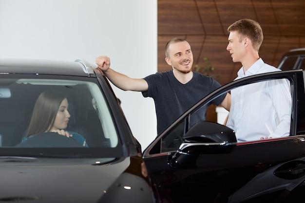 Przedstawiciel handlowy wyjaśnia zalety i wady nowego samochodu w salonie