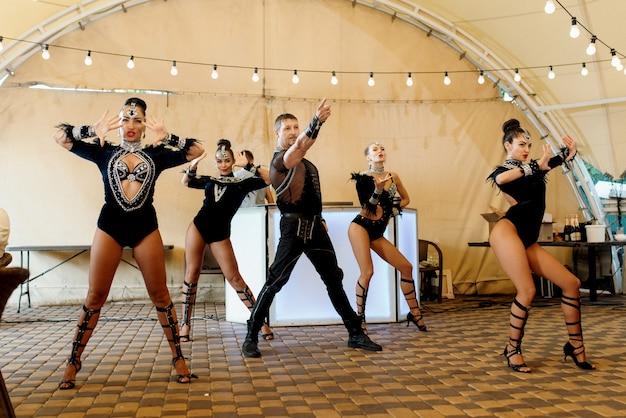 Przedstawienie show-baletu grupy tanecznej aktorów w jasnych kostiumach