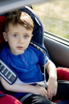 Przedszkola chłopiec siedzi w foteliku samochodowym