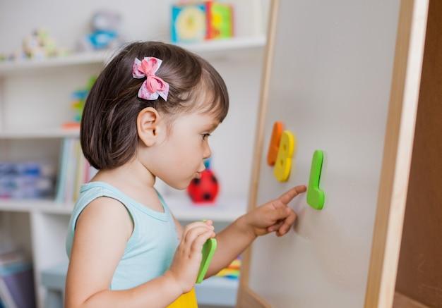 Przedszkola dziewczyna studiuje litery alfabetu.