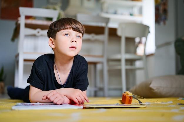 Przedszkolak kaukaski chłopiec leży na podłodze w domu, czyta książki i ogląda zdjęcia. koncepcja edukacji domowej