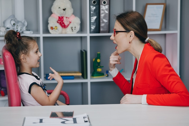Przedszkolak, mała dziewczynka mówiąca, ćwiczy dźwięki artykulacji podczas prywatnej lekcji z mamą