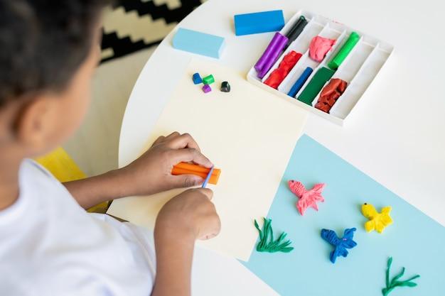 Przedszkolak rasy mieszanej tnie plastelinę w kolorze pomarańczowym na stole podczas robienia zdjęcia śmiesznej ryby na niebieskim papierze w przedszkolu
