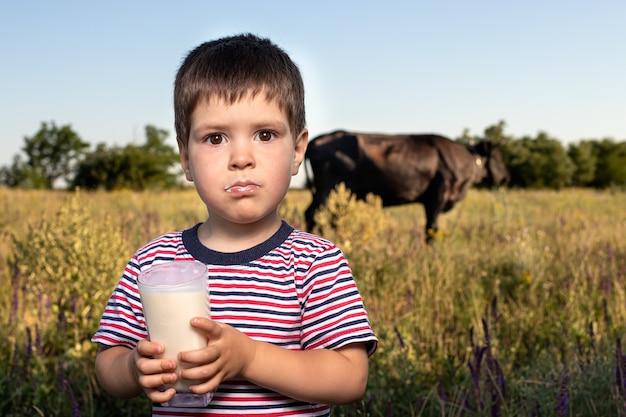 Przedszkolak trzyma szklankę z mlekiem na tle krowy.