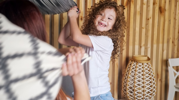 Przedszkolak z długimi, luźnymi kręconymi włosami walczy z brunetką, używając kolorowych poduszek i śmiejąc się z drewnianej ściany, z bliska