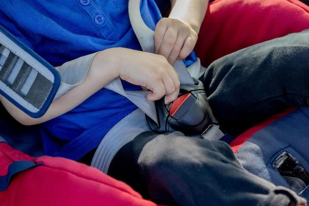 Przedszkolny uroczy chłopiec w wieku 3-4 lat siedzi w foteliku samochodowym i płacze podczas rodzinnej podróży samochodem, zły nastrój, negatywne emocje, wychowanie i koncepcja rodziny, lato na świeżym powietrzu
